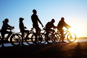 image of sporty company friends on bicycles outdoors against sunset.