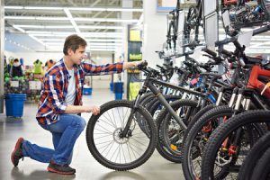 man checks bike before buying in sports shop